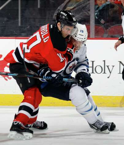 NEWARK, NJ - NOVEMBER 25: Matt Halischuk #15 of the Winnipeg Jets is held up by Peter Harrold #10 of the New Jersey Devils at the Prudential Center on November 25, 2013 in Newark, New Jersey.  The Jets defeated the Devils 3-1. (Photo by Bruce Bennett/Getty Images) ORG XMIT: 181111193 Photo: Bruce Bennett / 2013 Getty Images