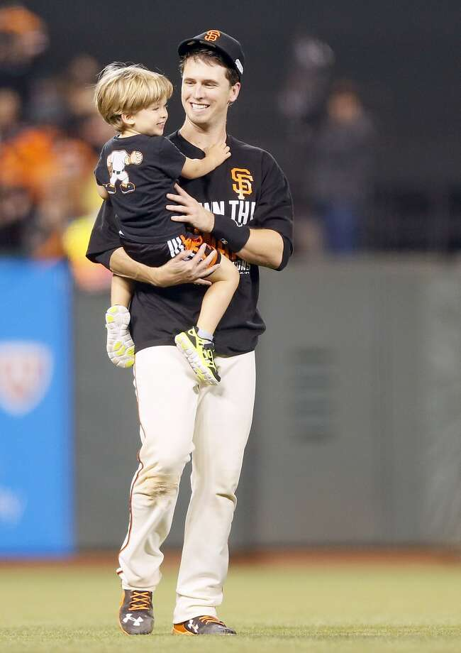 Giants Buster Posey carries his son, Lee, after Game 5 of the NLCS at AT&T Park on Thursday, Oct. 16, 2014 in San Francisco, Calif. Photo: Beck Diefenbach, Special To The Chronicle