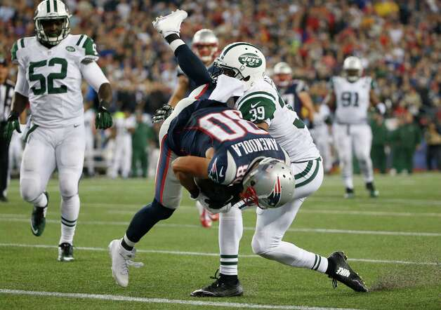 New England Patriots wide receiver Danny Amendola (80) tumbles across the goal line past New York Jets cornerback Antonio Allen (39) to score a touchdown during the second half of an NFL football game Thursday, Oct. 16, 2014, in Foxborough, Mass. (AP Photo/Elise Amendola)  ORG XMIT: FBO130 Photo: Elise Amendola / AP