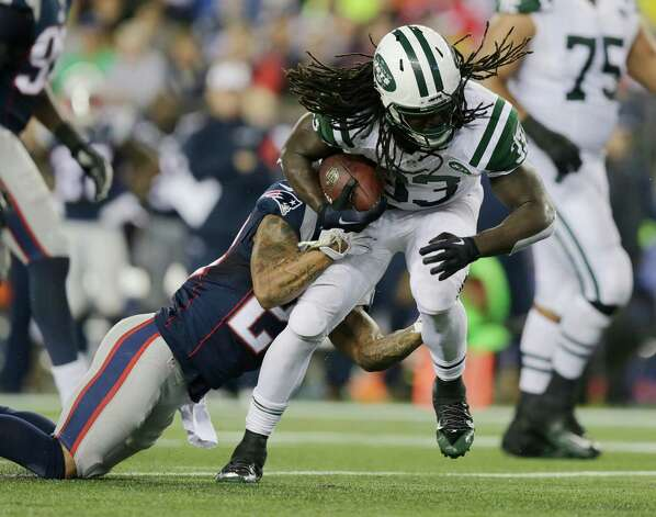 New England Patriots strong safety Patrick Chung, left, tackles New York Jets running back Chris Ivory during the first half of an NFL football game Thursday, Oct. 16, 2014, in Foxborough, Mass. (AP Photo/Charles Krupa)  ORG XMIT: FBO114 Photo: Charles Krupa / AP
