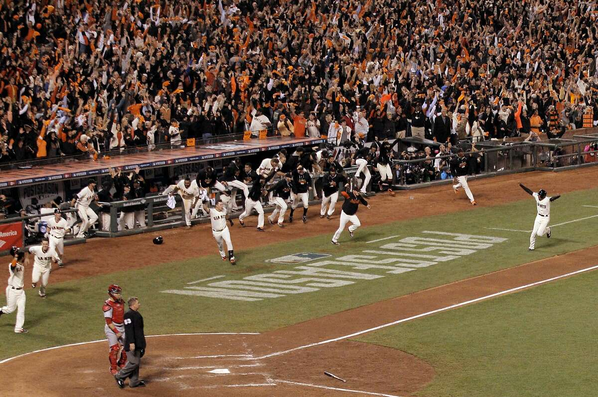 The Giants run from the dugout as Joaquin Arias, right, heads for home plate on Travis Ishikawa's three-run walk off home run during Game 5 of the NLCS at AT&T Park on Thursday, Oct. 16, 2014 in San Francisco, Calif.