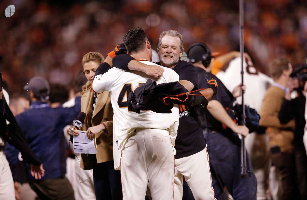 Bullpen catcher Bill Haye embraces Travis Ishikawa after the Giants defeated the Cardinals 6 to 3 in Game 5 of the NLCS at AT&T Park on Thursday, Oct. 16, 2014 in San Francisco, Calif.