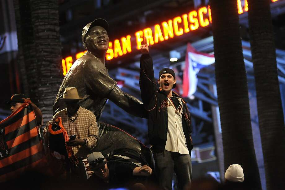 Giants fans climb on the statue of Willie Mays as they celebrate outside AT&T Park as the San Francisco Giants defeated the St. Louis Cardinals to win the NLCS,  in San Francisco, CA, on Thursday, Oct. 16, 2014. Photo: Michael Short, Special To The Chronicle