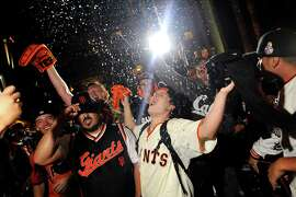 Champagne flies as fans celebrate outside AT&T Park as the San Francisco Giants defeated the St. Louis Cardinals to win the NLCS,  in San Francisco, CA, on Thursday, Oct. 16, 2014.