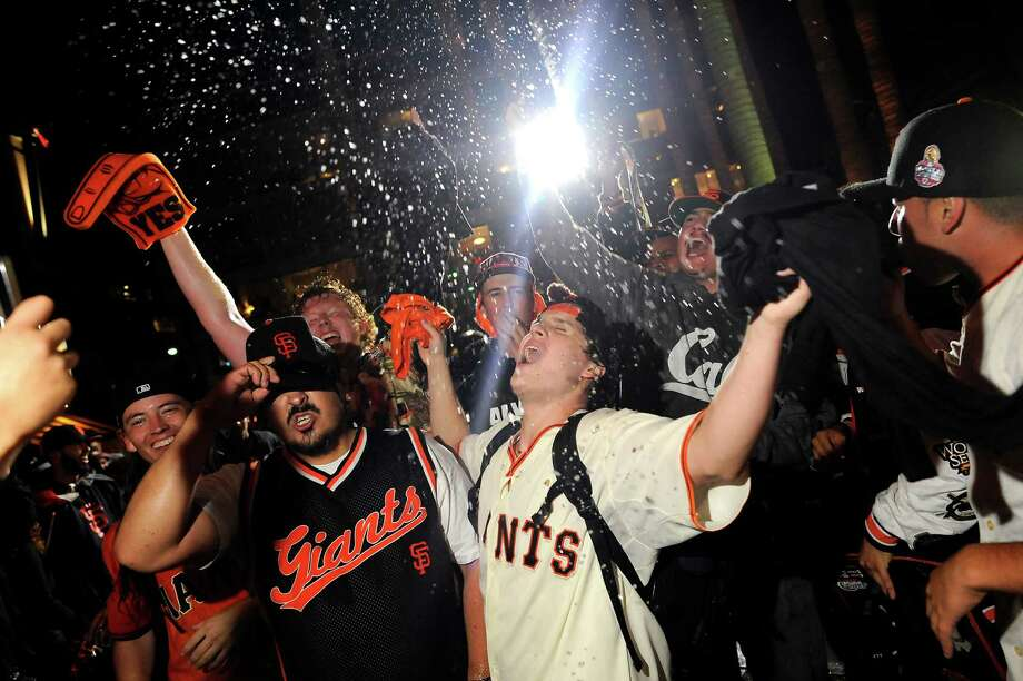 Champagne flies as fans celebrate outside AT&T Park as the San Francisco Giants defeated the St. Louis Cardinals to win the NLCS,  in San Francisco, CA, on Thursday, Oct. 16, 2014. Photo: Michael Short / Special To The Chronicle / ONLINE_YES