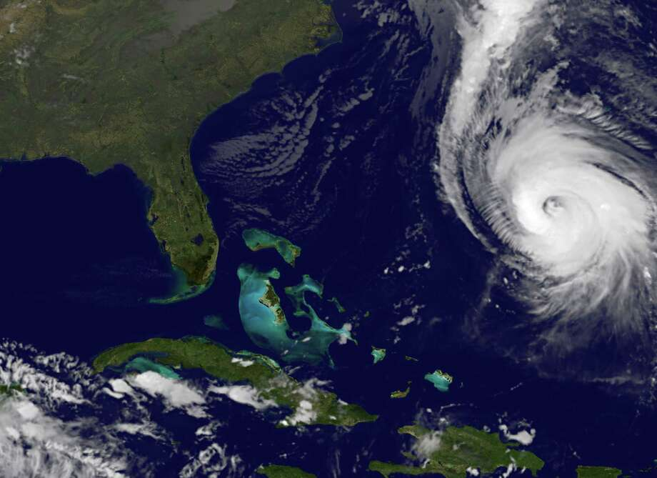 This image provided by NOAA taken at 11:15 p.m. EDT Thursday Oct. 16, 2014 shows Hurricane Gonzalo, right, as it approaches Bermuda. At 11 p.m. Gonzalo was approximately 340 miles south-southwest of Bermuda with maximum sustained winds of 140 mph moving north-northeast at 14 mph according to the National Hurricane Center. Gonzalo was expected to pass within 29 miles (46 kilometers) of Bermuda on Friday night, close enough to be considered a direct hit, the Bermuda Weather Service warned. Photo: NOAA, AP / NOAA