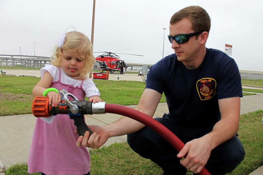 McKinleigh Thompson, 2, of Katy examines a fire hose held by West I-10 firefighter Brandon Dickinson at a spring safety event. Photo: Suzanne Rehak, Freelance Photographer