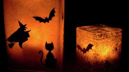 In this Oct. 13, 2014 photo, you can lighten up Halloween night with do-it-yourself luminaries. Attach black stickers to vellum or the waxy side of fr