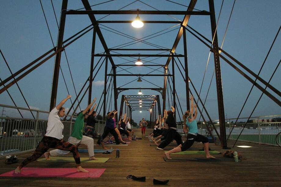 """Mobile Om founder Cassandra Fauss leads a yoga class on the Hays Street Bridge on Friday, Oct. 10, 2014. """"We believe that the most sacred space for yoga is not found inside any studio, temple or ashram, but instead, it is the space that is created within,"""" she said. Fauss teaches yoga twice a week on the bridge. (Kin Man Hui/San Antonio Express-News) Photo: Kin Man Hui,  Staff / San Antonio Express-News / ©2014 San Antonio Express-News"""