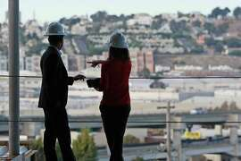 Demetrius Hobson (left), incoming principal of the future Willie L. Brown Jr. Middle School, and director of special projects Joyanna Balk check out the view from the construction site of the school gym, being built in San Francisco's Bayview district.