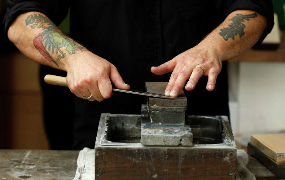 Cutler Josh Donald sharpens knives at Bernal Cutlery in S.F. Photo: Liz Hafalia / The Chronicle / ONLINE_YES