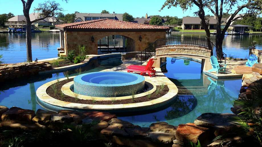 A lazy river pool winds around an island spa and fire pit as it skirts Lake LBJ. The owners of the Marble Falls house, which is featured in the 2014 Parade Home Tour, wanted to create a resort feel at home. Photo: Courtesy Matthew Bailey / Masters Touch Custom Homes
