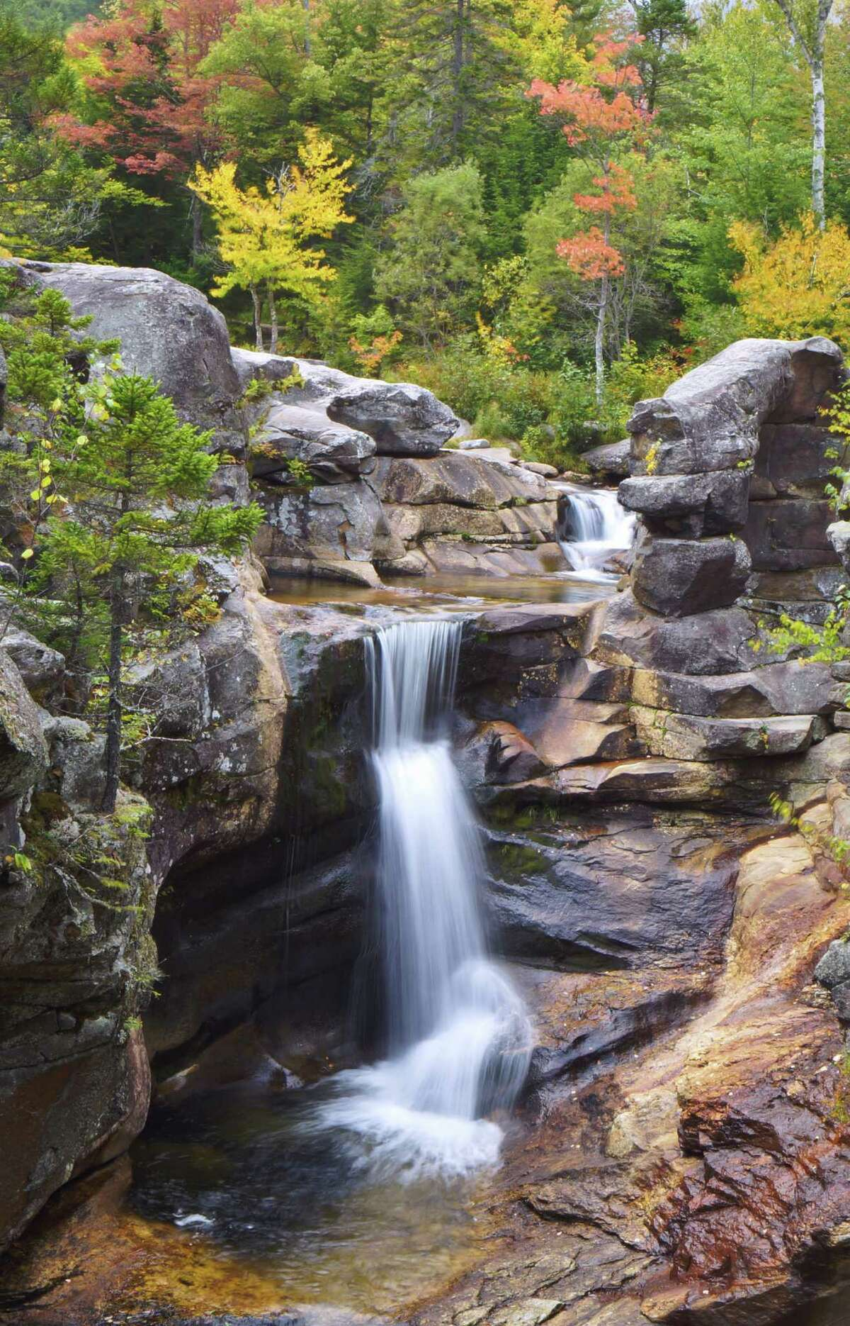 Fall colors have begun appearing near Screw Auger Falls in Grafton Notch State Park in Bethel, Maine.