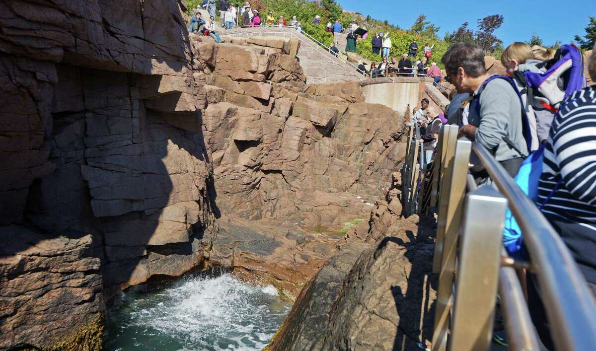 Onlookers watch the surf splash into the inlet known as Thunder Hole in Acadia National Park. When the surf is high, the ocean seems to roar as it approaches and retreats from holes in the rock.