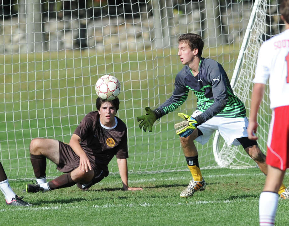 At right, Brunswick goal keeper Ben Rogers collects the ball after making a save as teammate, Thomas Errichetti (#13), defends, during the high school soccer match between Brunswick School and South Kent at Brunswick in Greenwich, Conn., Friday afternoon, Oct. 17, 2014. Photo: Bob Luckey / Greenwich Time