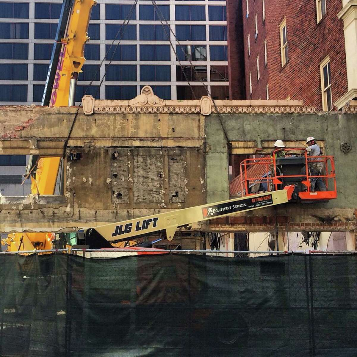 Construction workers remove the facade of a two-story building on Houston Street. They are demolishing three buildings on the 400 block of East Houston Street for a 10-story Hilton Garden Inn.