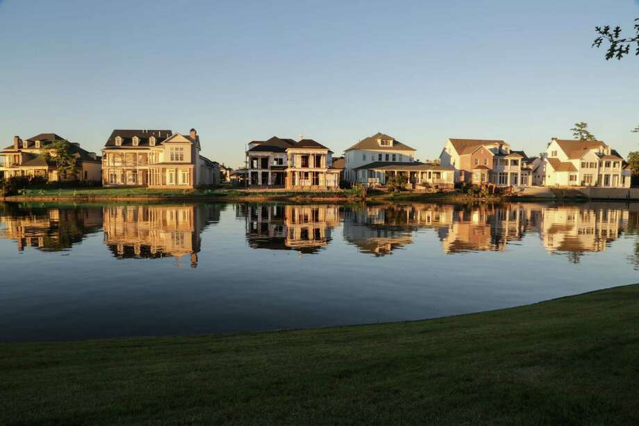 Homes reflect off the waters of Lake Woodlands in the  East Shore, neighborhood in The Woodlands, TX October 15, 2014. East Shore, is  a 169-acre enclave on the eastern edge of 200-acre Lake Woodlands. (Billy Smith II / Chronicle) Photo: Billy Smith II, Staff / © 2014 Houston Chronicle