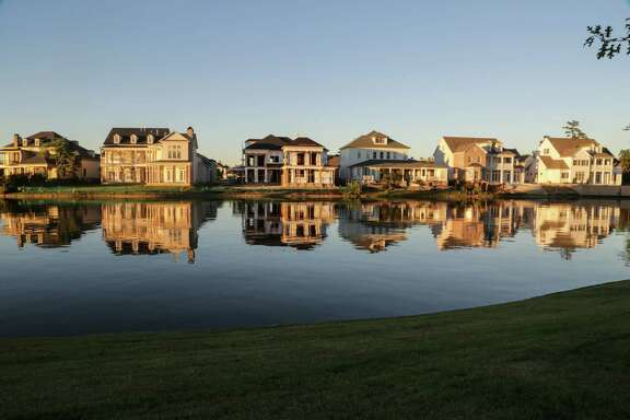 Homes reflect off the waters of Lake Woodlands in the  East Shore, neighborhood in The Woodlands, TX October 15, 2014. East Shore, is  a 169-acre enclave on the eastern edge of 200-acre Lake Woodlands. (Billy Smith II / Chronicle)