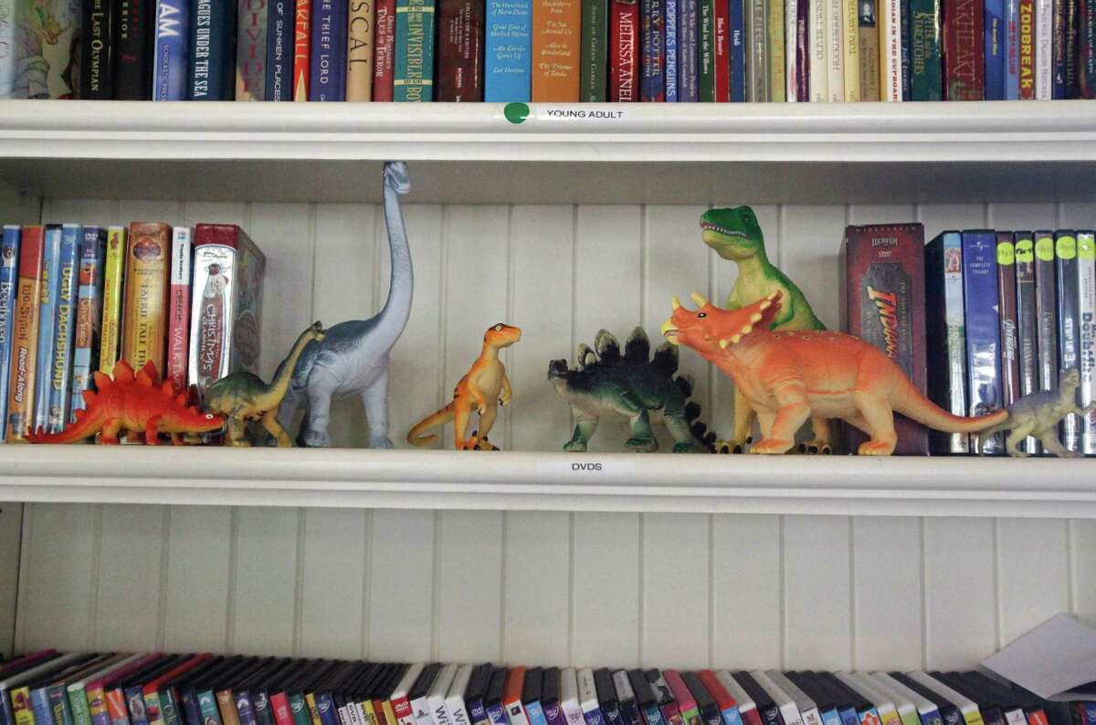 """Plastic dinosaurs sit on a shelf with DVDs accompanied by young adult books and movies for children of all ages in the activities room at George Mark Children's House Oct. 1, 2014 in San Leandro, Calif. The House is a non-profit organization that administers palliative care to severely ill children and provides support for their families. Founded 10 years ago, the home provides transitional care, end of life care and respite care to patients with a ?'life-limiting diagnosis?"""" from birth to 21-years-old."""
