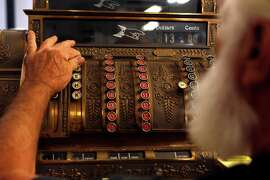 Jack Wood operates the nearly 100-year-old National Cash Register at Young's Market in Taylorsville (Plumas County).
