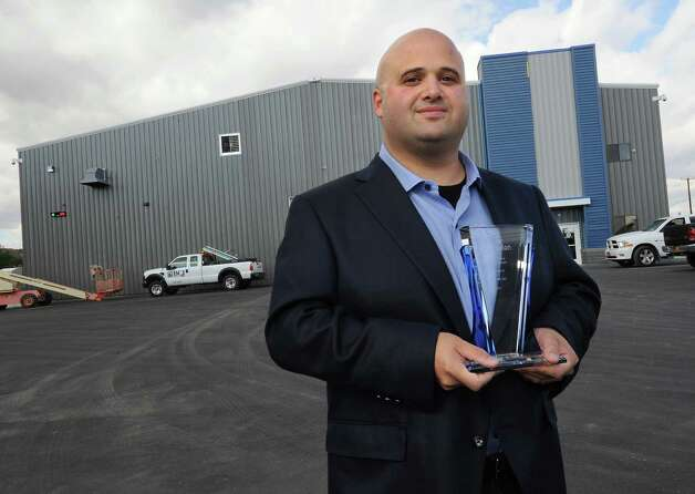 President Brian Hemlock holds his Exelon award outside the operations building at TCI of New York on Friday, Oct. 17, 2014 in Coeymans, N.Y. The electronics recycling company recently rebuilt and opened their new headquarters at Port of Coeymans. (Lori Van Buren / Times Union) Photo: Lori Van Buren / 10029071A