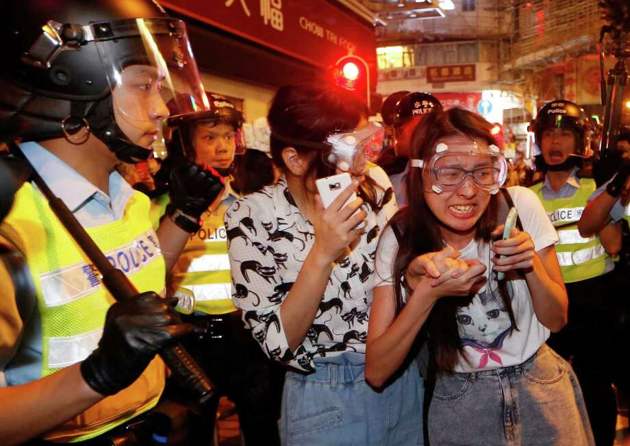 Protesters cry as some of the protesters are beaten by riot police in the occupied area in the Mong Kok district of Hong Kong, early Saturday, Oct. 18, 2014. New scuffles broke out Friday night between Hong Kong riot police and pro-democracy activists in a district where police cleared protesters earlier in the day.  (AP Photo/Kin Cheung) Photo: Kin Cheung, STF / AP