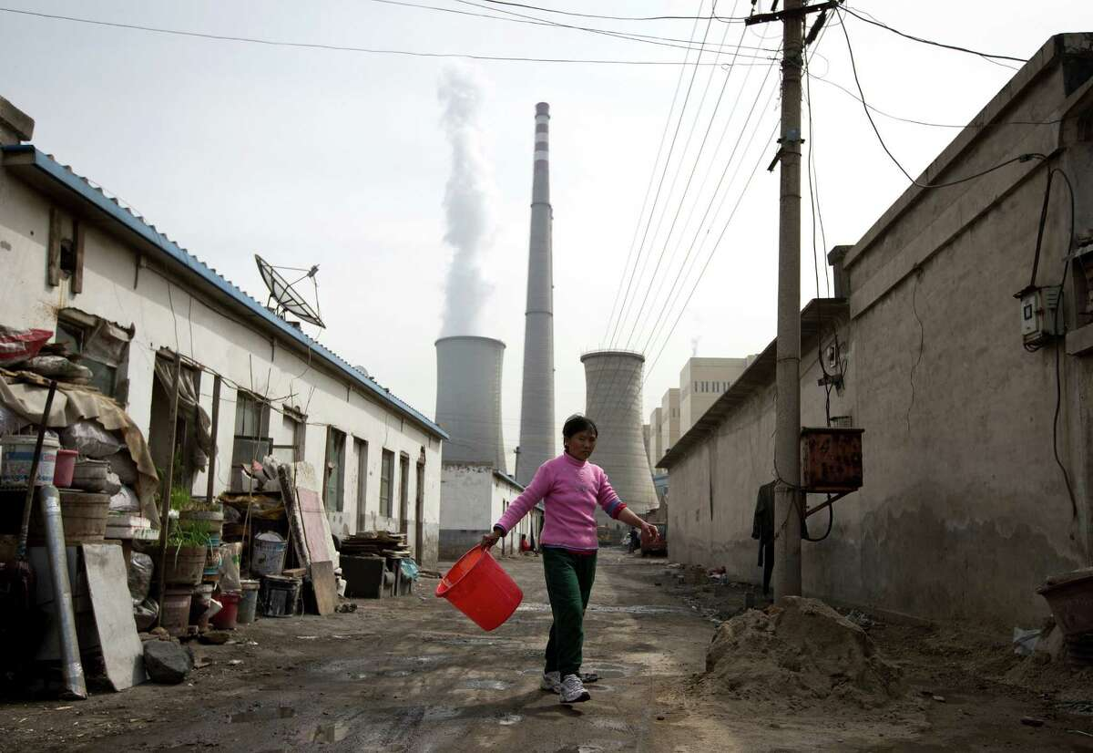 In this file photo, a woman walks through a neighborhood near a coal-fired power plant in Beijing. Carbon dioxide levels in the atmosphere reached a record high in 2013. Readers weigh in on climate change.