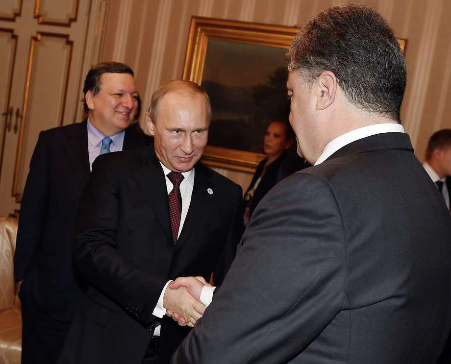 Russian President Vladimir Putin, left, and Ukraine's President Petro Poroshenko meet on the sidelines of the  ASEM summit of European and Asian leaders in Milan, northern Italy, Friday, Oct. 17, 2014. Russian President Vladimir Putin is looking to get relief from Western economic sanctions imposed since Russia's annexation of the Crimean Peninsula and its support for a pro-Russia insurgency in eastern Ukraine. To that end, he has scheduled a series of meetings on the sidelines of a two-day ASEM summit of European and Asian leaders. (AP Photo/Daniel Dal Zennaro, POOL) Photo: Daniel Dal Zennaro, POOL / ANSA POOL