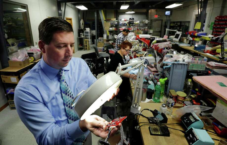 Company owner Scott Schober uses a magnifier to look at a circuit board for a cellular telephone detector at Berkeley Varitronic Systems in Metuchen, N.J. Berkeley's bank account was hacked earlier this year, and $50,000 was taken. , Photo: Mel Evans, STF / AP
