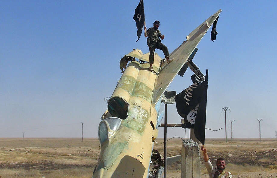 The Islamic State group posted this image on Aug. 27 of fighters waving the militants' flag from a damaged fighter jet at the al-Tabaqa air base in Raqqa, Syria. Photo: Uncredited, HONS / Raqqa Media Center of the Islami