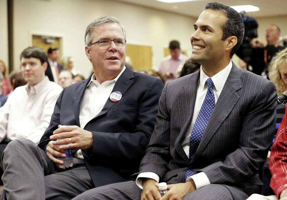 Former Florida Gov. Jeb Bush, left, sits with his son George P. Bush before speaking to supporters at Hardin-Simmons University, Tuesday, Oct. 14, 2014, in Abilene, Texas. Jeb Bush heads into West Texas to campaign for his son who is on the ballot this November as a candidate for state land commissioner. (AP Photo/LM Otero) Photo: LM Otero, STF / AP
