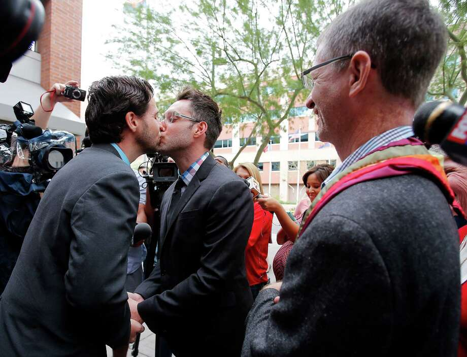 Kevin Patterson, left, and David Larance kiss after exchanging vows before the Rev. John Dorhaer, right, in Phoenix. Gay marriage became legal in Arizona after the state said it wouldn't challenge a federal court decision handed down Friday. Photo: Rick Scuteri, FRE / FR157181 AP