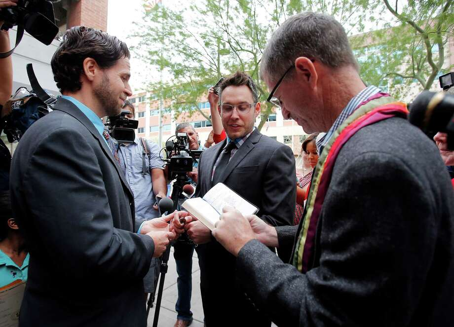 Kevin Patterson, left, and David Larance exchange vows by Rev. Dr. John Dorhaer, right, Friday, Oct. 17, 2014, in Phoenix. Gay marriage has become legal in Arizona after the state's conservative attorney general said Friday that he wouldn't challenge a federal court decision that cleared the way for same-sex unions in the state. (AP Photo/Rick Scuteri) Photo: Rick Scuteri, FRE / FR157181 AP