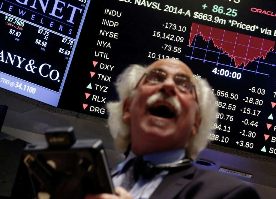 """FILE - In this Wednesday, Oct. 15, 2014, file photo, trader Peter Tuchman watches a screen above the floor of the New York Stock Exchange at the closing bell, as the Dow Jones industrial average plummeted as much as 460 points in afternoon trading, then clawed back much of the ground it lost. Europe's economy is sputtering, oil prices are falling and stocks are swinging wildly. And Wall Street's long dormant """"fear index"""" predicts more turbulence ahead. (AP Photo/Richard Drew, File) Photo: Richard Drew, STF / AP"""