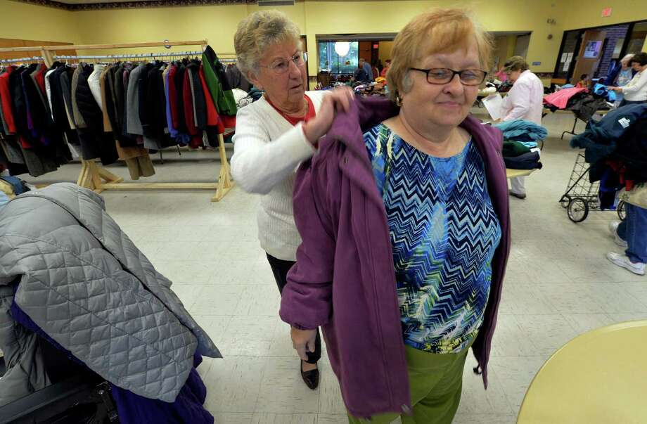 Koanne Kowalski is fitted for a new coat by volunteer Eleanor McCoy at the Coats for the Community Program Friday afternoon Oct 17, 2014 at the Cohoes Senior Citizen Center  in Cohoes, N.Y.     (Skip Dickstein/Times Union) Photo: SKIP DICKSTEIN / 10028824A