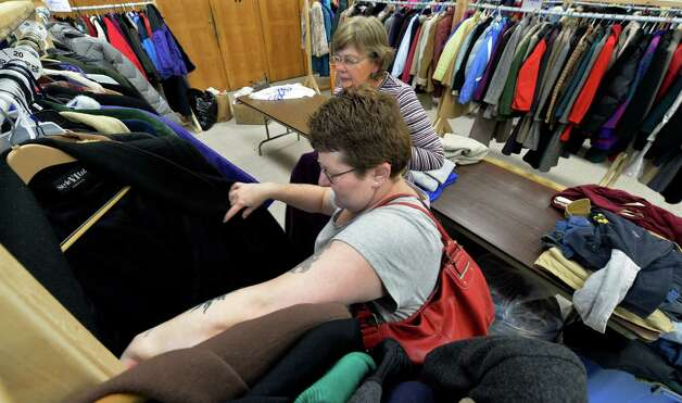 Lee Devlin, foreground, looks for a new coat with the aid of volunteer Kathy Ryan at the Coats for the Community Program Friday afternoon Oct 17, 2014 at the Cohoes Senior Citizen Center  in Cohoes, N.Y.     (Skip Dickstein/Times Union) Photo: SKIP DICKSTEIN / 10028824A