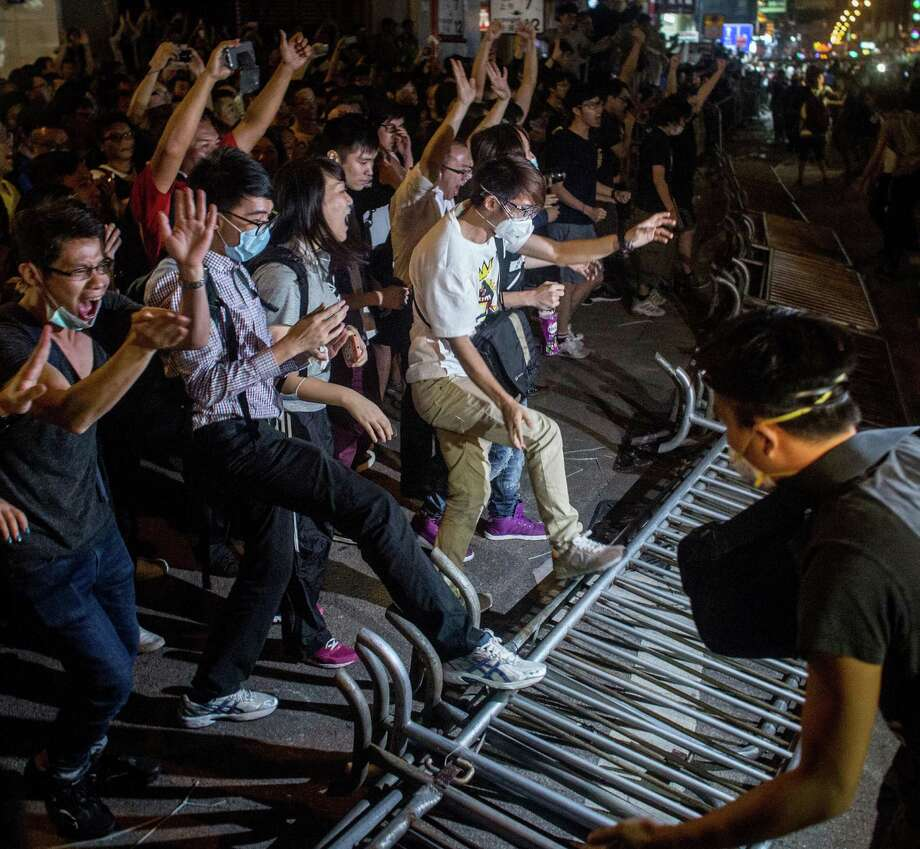 Pro-democracy protesters celebrate as they break down a police barricade while taking back a street in the Mong Kok area of Hong Kong. Photo: Chris McGrath / Getty Images / 2014 Getty Images