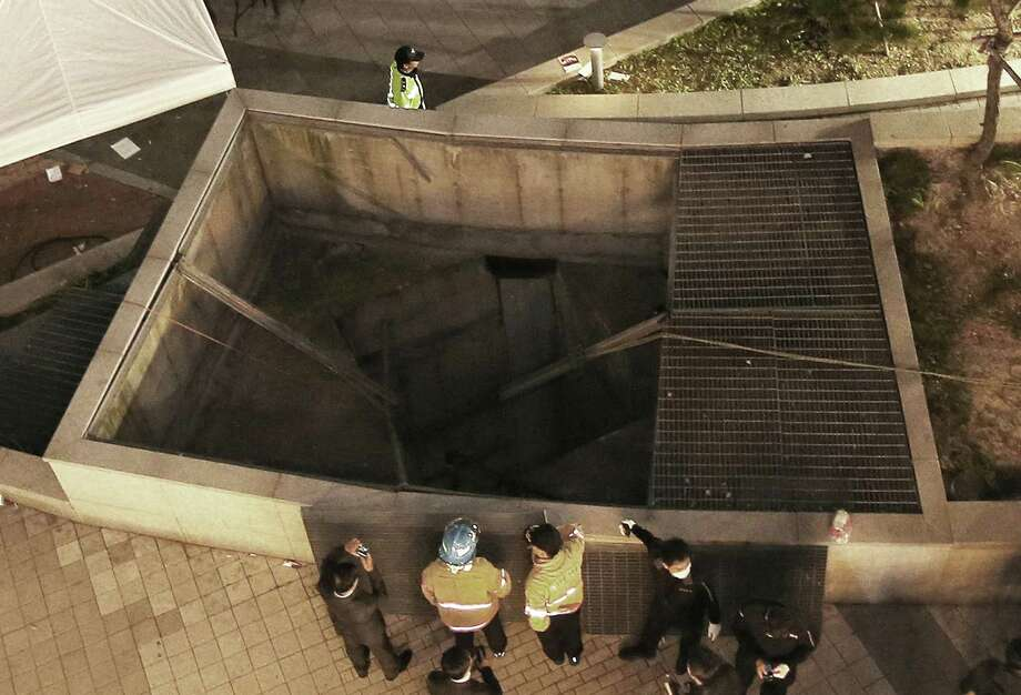Rescue workers stand around a collapsed ventilation grate at an outdoor theater in Seongnam, south of Seoul, South Korea, Friday, Oct. 17, 2014. Fourteen people were feared dead Friday after the ventilation grate collapsed during a concert by popular girls' band 4Minute, officials said. (AP Photo/Yonhap, Shin Young-geun) KOREA OUT Photo: Shin Young-geun, SUB / Yonhap