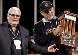 General manager Brian Sabean and manager Bruce Bochy savor the moment and the attendant emotions after the Giants took the trophy for capturing the National League pennant, their third in five years.