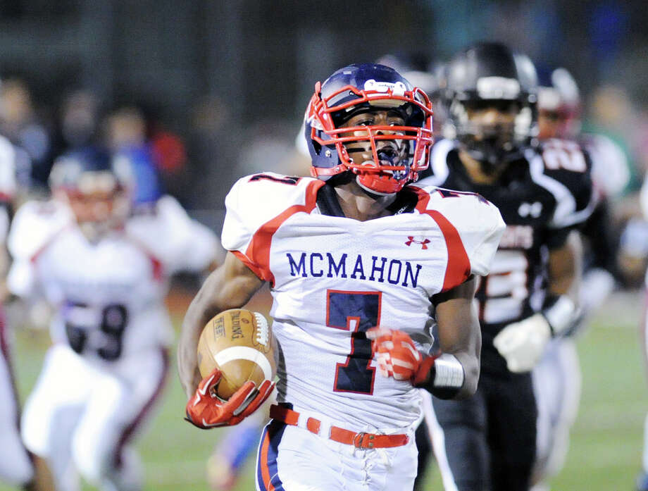 At center, Kentrell Snider (#7) of Brien McMahon scores his first third quarter rushing touchdown as he gets past Stamford's Darwin Leon (#23), at right, during the high school football game between Stamford High School and Brien McMahon High School at Stamford, Friday night, Oct. 17, 2014. Brien McMahon defeated Stamford, 49-21. Photo: Bob Luckey / Greenwich Time
