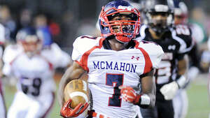 At center, Kentrell Snider (#7) of Brien McMahon scores his first third quarter rushing touchdown as he gets past Stamford's Darwin Leon (#23), at right, during the high school football game between Stamford High School and Brien McMahon High School at Stamford, Friday night, Oct. 17, 2014. Brien McMahon defeated Stamford, 49-21.