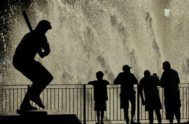 Kansas City Royals fans stand in the mist of fountains at Kauffman Stadium.