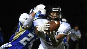 Ansonia receiver Tyler Bailey (5) drops a pass defended by Newtown's Joseph Santella in the high school football game between Newtown and Ansonia at Newtown High School in Newtown, Conn. Friday, Oct. 17, 2014.