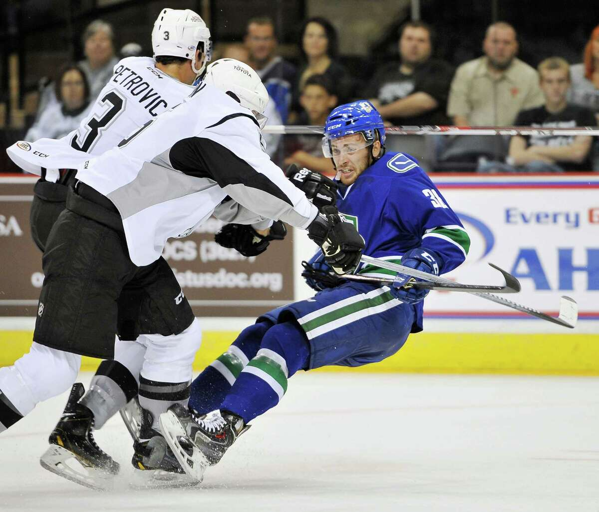 San Antonio Rampage players Alex Petrovic, left, and Greg Zanon, take down Utica Comets' Wacey Hamilton during the first period of an AHL hockey game, Friday, Oct. 17, 2014, in San Antonio. (Darren Abate/AHL)