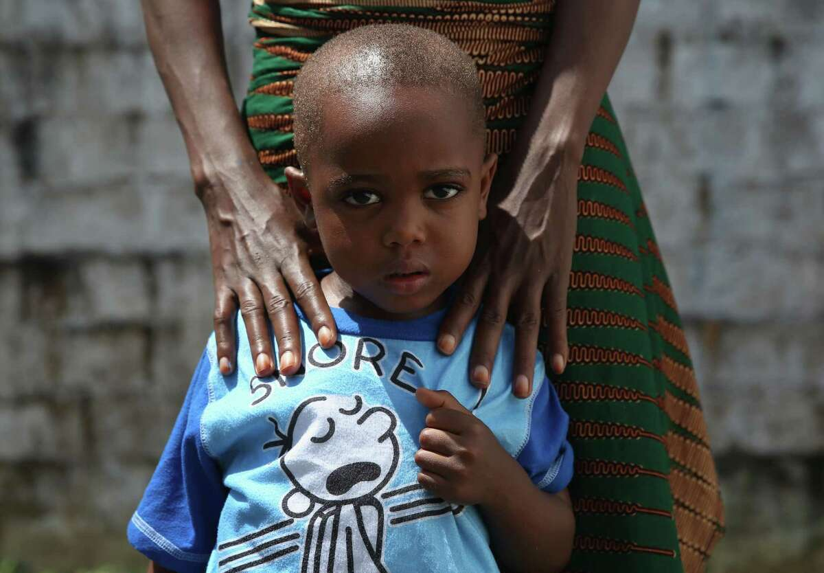 Ebola survivor James Mulbah, 2, stands with his mother, Tamah Mulbah, 28, who also recovered from Ebola in the low-risk section of the Doctors Without Borders (MSF), Ebola treatment center after survivors' meeting on October 16, 2014 in Paynesville, Liberia. The virus has a 70 percent mortality rate, according to the World Health Organization, but leaves survivors immune to the strain that sickened them.