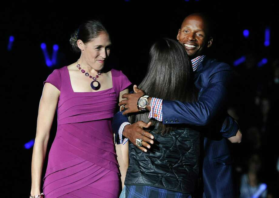NBA player and former Connecticut basketball player Ray Allen, right, hugs WNBA and former Connecticut basketball  player Sue Bird as former player Rebecca Lobo, left, watche, during at the men's and women's NCAA college basketball teams' First Night event, Friday, Oct. 17, 2014, in Storrs, Conn. (AP Photo/Jessica Hill) Photo: Jessica Hill, Associated Press / Associated Press