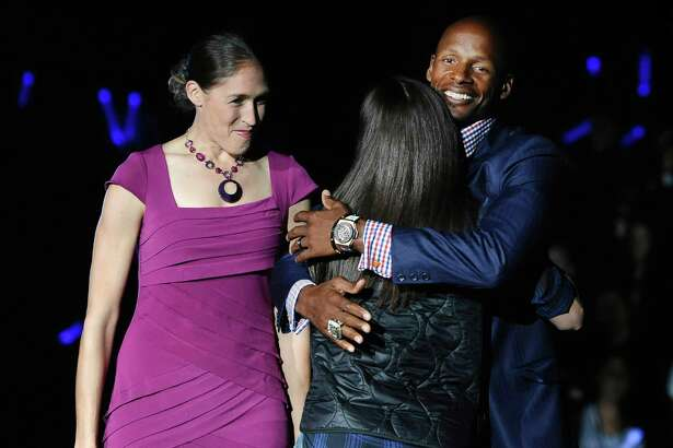 NBA player and former Connecticut basketball player Ray Allen, right, hugs WNBA and former Connecticut basketball player Sue Bird as former player Rebecca Lobo, left, watche, during at the men's and women's NCAA college basketball teams' First Night event, Friday, Oct. 17, 2014, in Storrs, Conn. (AP Photo/Jessica Hill)