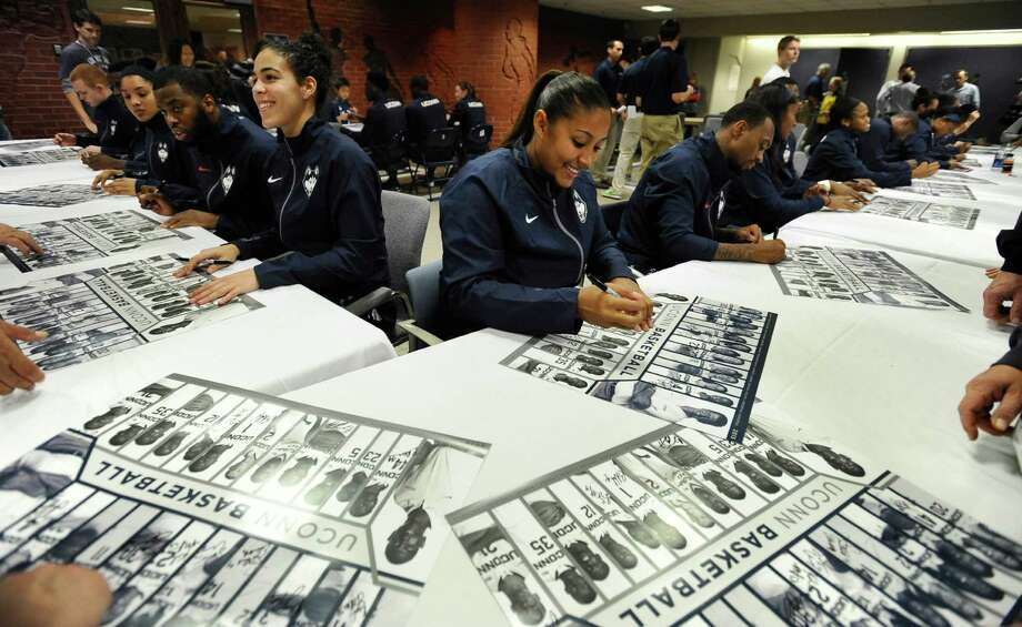 Connecticut's Kia Nurse, left center, and Kaleena Mosqueda-Lewis, right center, sign autographs during the women's and men's NCAA college basketball teams' First Night event, Friday, Oct. 17, 2014, in Storrs, Conn. (AP Photo/Jessica Hill) Photo: Jessica Hill, Associated Press / Associated Press