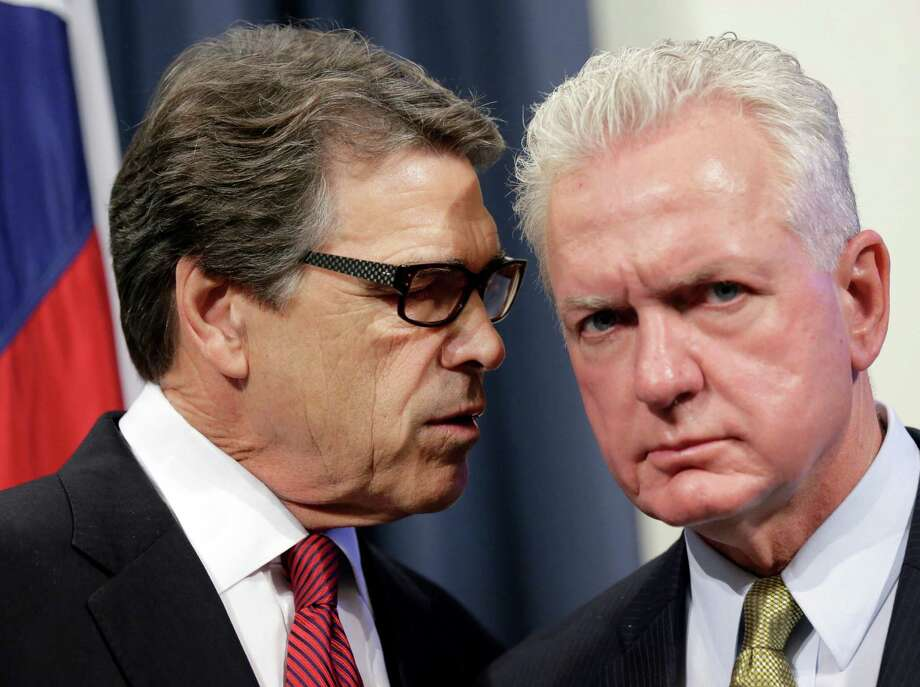Gov. Rick Perry confers Friday with Dr. Brett Giroir, director of the task force he assembled to tackle Ebola. Photo: Eric Gay, STF / AP