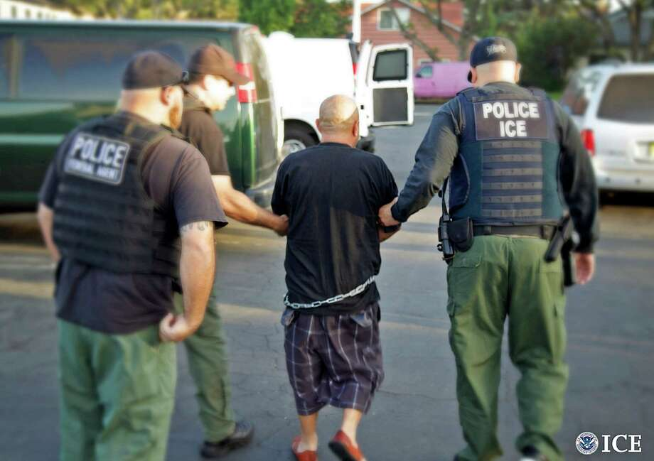 In this Tuesday, Oct. 14, 2014 photo provided by the U.S. Bureau of Immigration and Customs Enforcement (ICE), agents take a person into custody during an immigration sweep in Ontario, Calif. Immigration officials say local authorities across the U.S. released thousands of immigrants from jails this year despite efforts to take them into federal custody, including more than 3,000 with previous felony charges or convictions. They highlight the friction between the federal government and police and sheriff's departments, some of which say holding immigrants beyond their release dates harms community policing efforts. (AP Photo/U.S. Bureau of Immigration and Customs Enforcement) ORG XMIT: LA102 / U.S. Bureau of Immigration and Customs Enforcement